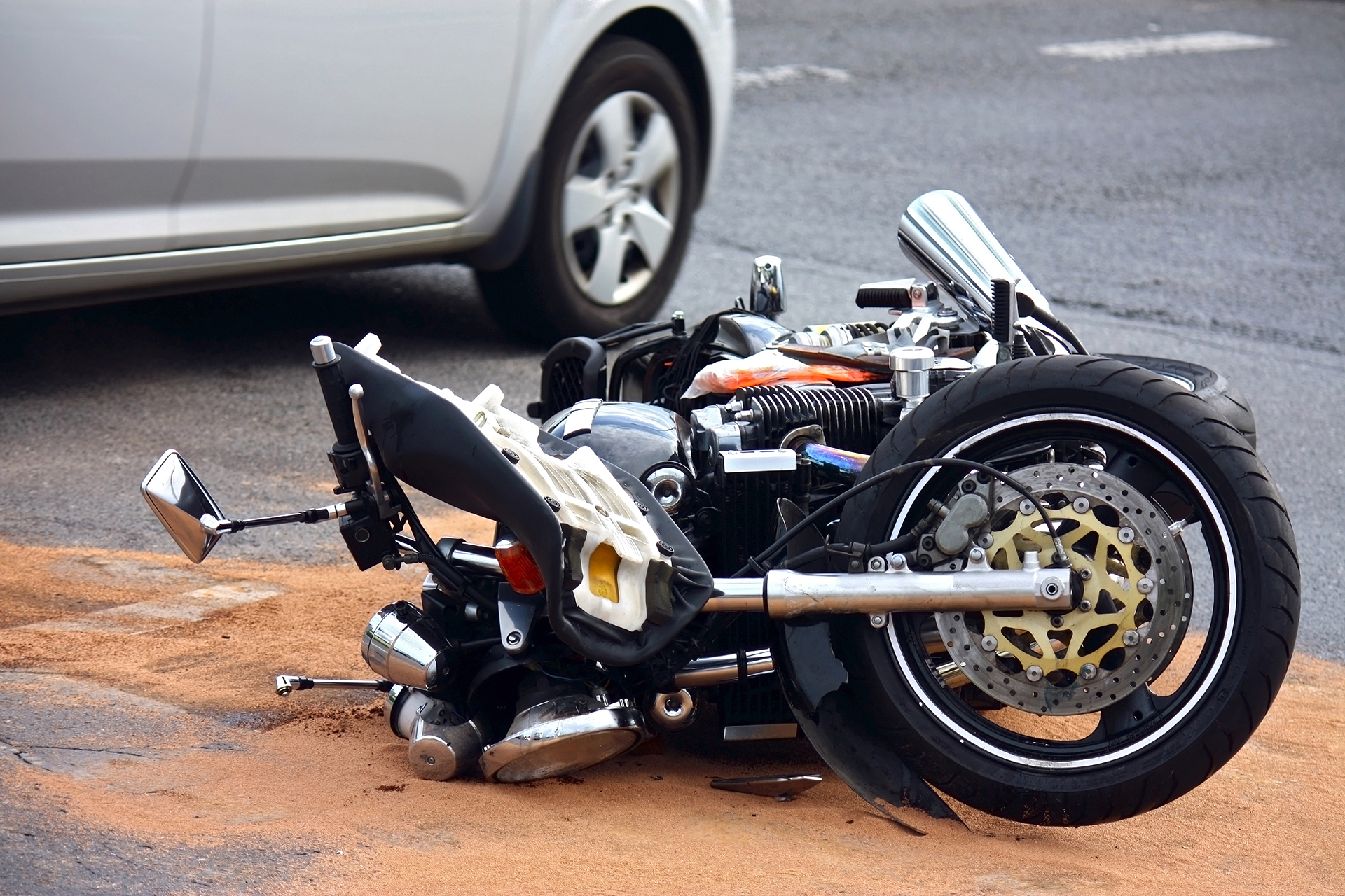 Photo of motorcycle laying on the road after an accident